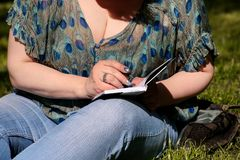 Woman and student sitting on grass, takes notes in notebook, learning and writes thoughts, writes book. stock photography