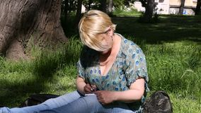 Woman and student sitting on grass, takes notes in notebook, learning and writes thoughts, writes book. Woman and student sitting on grass, takes notes in stock video footage