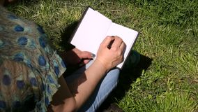 Woman and student sitting on grass, takes notes in notebook, learning and writes thoughts, writes book. Woman and student sitting on grass, takes notes in stock video