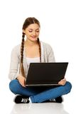 Woman student sitting with laptop. Happy teenage woman sitting with laptop Royalty Free Stock Image
