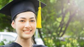 Woman student smiles and feel happy in  graduation gowns and cap. The woman student smiles and feel happy in  graduation gowns and cap Stock Photos
