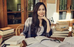 Woman student studying with a lot of paper books stock photo