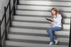 Woman or student with tablet pc sitting on stairs stock photography