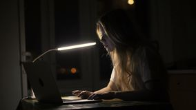 Woman student using laptop computer for online education in dark room. Young woman using touch pad on notebook for watching photo in social network stock footage