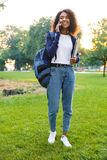 Woman student walking in the park holding laptop talking by mobile phone. Image of young beautiful african woman student walking in the park holding laptop stock photography