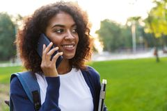Woman student walking in the park holding laptop talking by mobile phone. Image of young beautiful african woman student walking in the park holding laptop royalty free stock photos