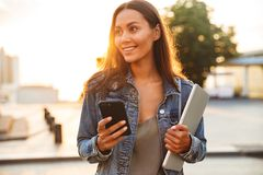 Woman student walking in the park using mobile phone. stock photo