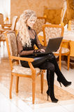 Woman-student works on black laptop Royalty Free Stock Photos