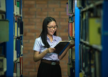 Woman students are a handful of books The bookshelf royalty free stock image