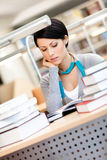 Woman studies at the library. Woman surrounded with piles of books reads sitting at the desk at the library Royalty Free Stock Photos