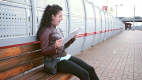 Woman studies a map and yawns. Waiting for train on platform stock footage