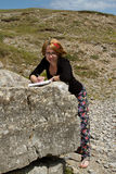 Woman studies rock. A pretty young woman works in the outdoors studying limestone rock with a notebook and pen Stock Image