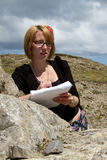 Woman studies rock. A pretty young woman works in the outdoors studying limestone rock with a notebook and pen Royalty Free Stock Image