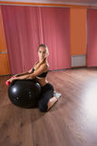 Woman in Studio with Inflatable Ball and Weights Royalty Free Stock Image