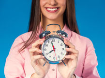 Woman in studio. Portrait of a young beautiful business woman with alarm clock isolated on a blue background Stock Photo