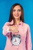 Woman in studio. Portrait of a young beautiful business woman with alarm clock isolated on a blue background Royalty Free Stock Photos