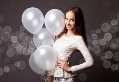 Woman in studio with white balloons Royalty Free Stock Image