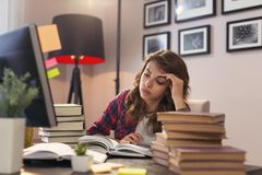 Woman studying. Beautiful young woman sitting at a desk at her home office, studying and working late stock photos