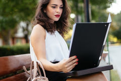 Woman studying on bench. Outdoors Stock Photos
