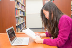 Woman studying. Woman with book and laptob studying in library Royalty Free Stock Photos