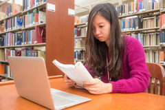 Woman studying. Woman with book and laptob studying in library Stock Photography