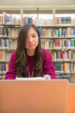 Woman studying. Woman with book and laptob studying in library Stock Images
