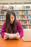 Woman studying. Woman with book and laptob studying in library Stock Photos