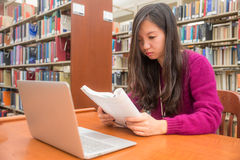 Woman studying. Woman with book and laptob studying in library Royalty Free Stock Photo