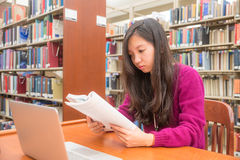 Woman studying. Woman with book and laptob studying in library Stock Photo