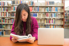 Woman studying. Woman with book and laptob studying in library Stock Image