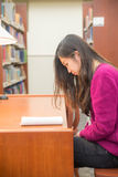 Woman studying. Woman with book studying in library Stock Photo