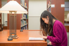 Woman studying. Woman with book studying in library Stock Photos