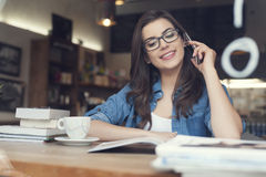Woman studying in cafe. Smiling young woman talking on phone in cafe Stock Photo