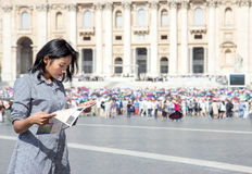 Woman studying a city map. At St. Peter`s Basilica in Vatican, Rome, Italy Stock Photos