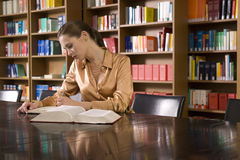 Woman Studying At Desk In Library. Beautiful young woman studying at desk in library Royalty Free Stock Images