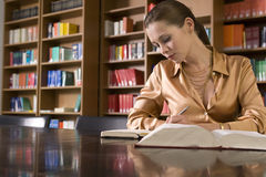 Woman Studying At Desk In Library Stock Images