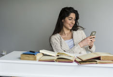 Woman  studying for exams with phone in the hand. Female student sitting at the desk with a  pile of study books and mobile phone Royalty Free Stock Image