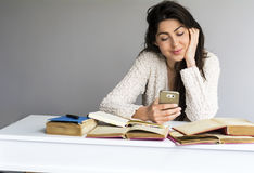 Woman  studying for exams with phone in the hand Stock Images