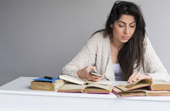 Woman  studying for exams with phone in the hand Royalty Free Stock Photography
