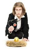 Woman studying a golden egg. Royalty Free Stock Photography
