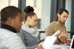 Woman studying hard for exams in library. Young african american women reading notes with classmates studying around in university library. Students preparing Royalty Free Stock Images