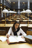 Woman studying in library. Young attractive woman sitting at desk in old university library studying books, front view Stock Photography