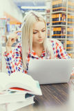 Woman studying in library. Young pretty woman studying in library Stock Photography