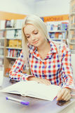 Woman studying in library. Young pretty woman studying in library Royalty Free Stock Image
