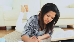 Woman studying while lying on the flloor Stock Photos