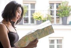 Woman studying map at the open window Stock Images