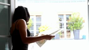 Woman studying map at the open window stock footage