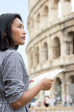 Woman studying the map at Rome. Asian tourist on a tour of Rome`s historic center. Woman studying the map of the city near the Colosseum, Roma, Italy Royalty Free Stock Photos