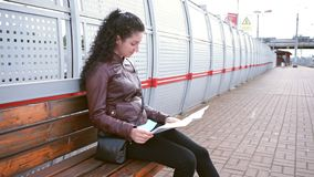 Woman are studying map and waiting. Brunette woman are studying map. Waiting for train on platform stock video footage