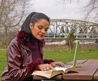 Woman Studying at Park with Laptop Computer. Young professional woman is studying in the park with a laptop computer and book.  Model is in her late 30's and is Stock Image